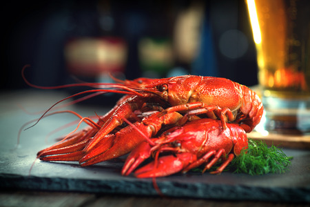 Red boiled crayfish with lemon and herbs on stone slate. Crawfish closeup