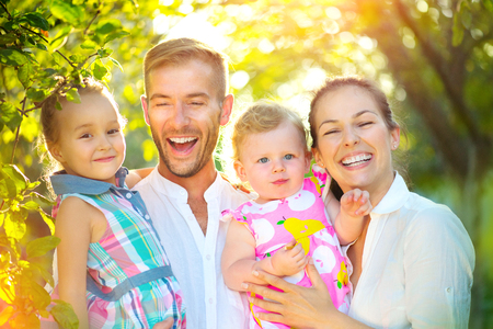 Happy joyful young family with little kids having fun outdoors Stock Photo - 80688544