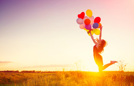 Beauty girl running and jumping on summer field with colorful air balloons over sunset sky Banque d'images