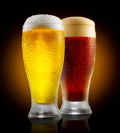 Craft beer. Two glasses of cold light and dark beer isolated on black background Stock Photo