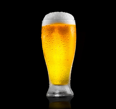 Beer. Glass of cold beer with water drops. Craft beer isolated on black background Banco de Imagens