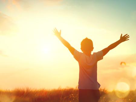 Little boy raising hands over sunset sky, enjoying life and nature