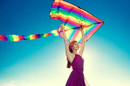 Beauty redhead girl with flying colorful kite over clear blue sky