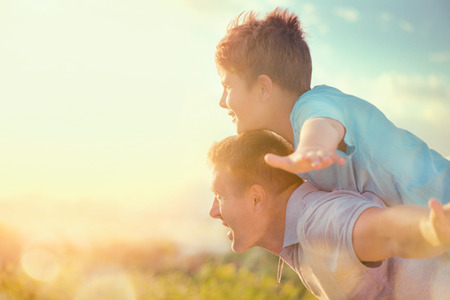 Happy father and son having fun over beautiful sky outdoors. Summer holidays, vacation