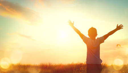 Little boy raising hands over sunset sky, enjoying life and nature