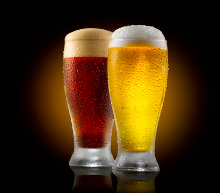 Craft beer. Two glasses of cold light and dark beer isolated on black background Banco de Imagens