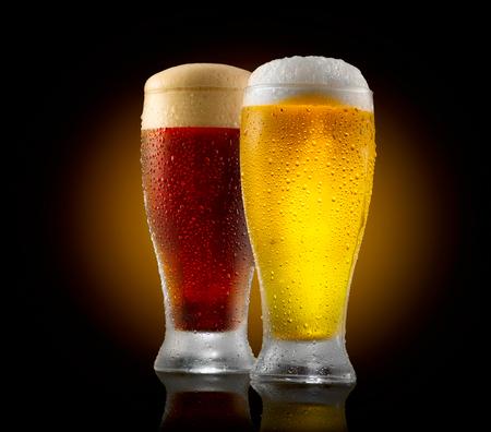 Handgemachtes Bier. Zwei Gläser kaltes Licht und dunkles Bier auf schwarzem Hintergrund isoliert Standard-Bild - 81175418