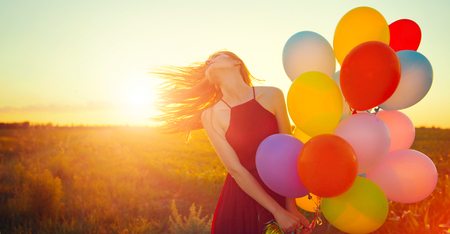 Beauty romantic girl on summer field with colorful air balloons over clear sky