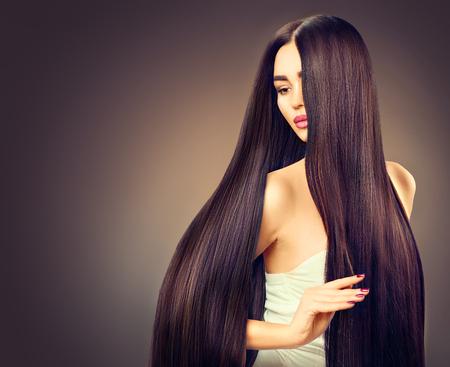 暗い背景上長いストレートの黒髪の美しいブルネット モデルの女の子 写真素材