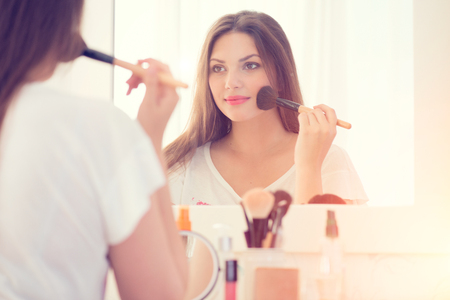 bedroom: Beautiful girl looking in the mirror and applying makeup