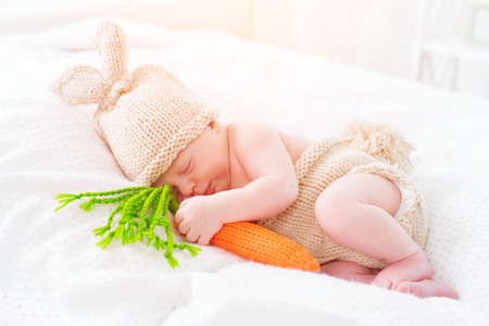 white: Cute two weeks old newborn baby boy wearing knitted bunny costume. Sweet baby portrait Stock Photo