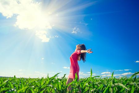 Schönheit Mädchen auf Sommer Feld steigt Hände über blau klaren Himmel. Glückliche junge gesunde Frau genießen Natur im Freien