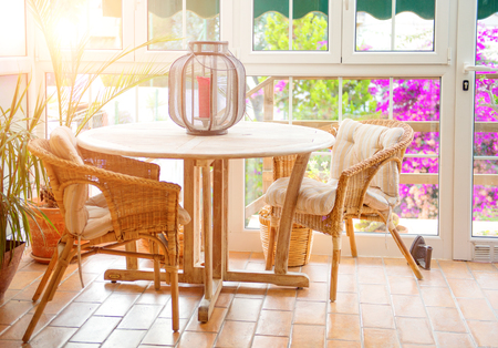 Interior of sunny empty summer cafe terrace with table and wicker chairs Stock Photo
