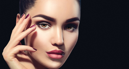 Beauty brunette woman with perfect makeup isolated on black background. Professional holiday make-up Banque d'images