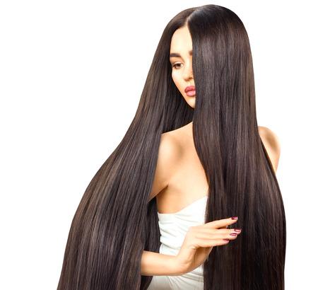 セクシーなブルネットのモデルの女の子彼女の長い滑らかな光沢のあるストレートの髪に触れて
