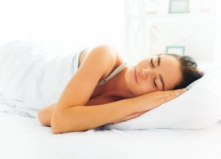 Beauty brunette girl sleeping in her comfortable bed Stock Photo