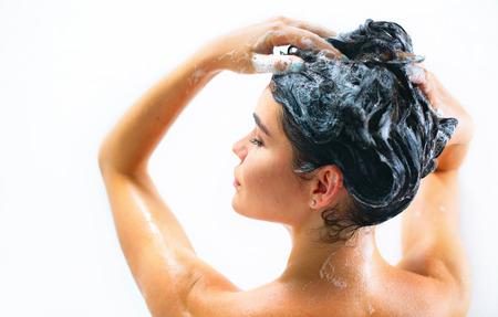 Belle femme modèle sexy prenant la douche et laver ses longs cheveux noirs avec un shampooing Banque d'images - 82234651