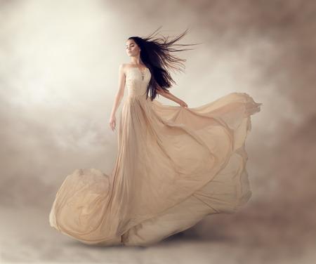 Mode model in mooie luxe beige vloeiende chiffon jurk