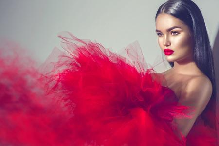 豪華なブルネットのモデル スタジオでポーズをとって赤いドレスの女性