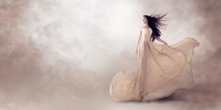 people: Fashion model in beautiful luxury beige flowing chiffon dress