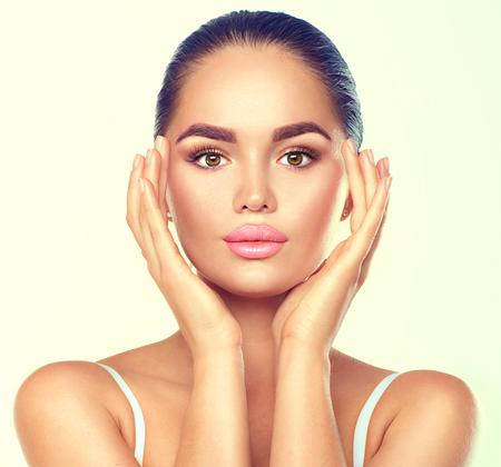 Beauty brunette spa vrouw met perfecte make-up aanraken haar gezicht. Huidverzorging concept