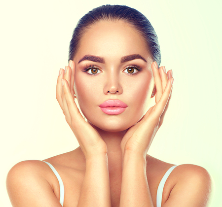Beauty brunette spa woman with perfect makeup touching her face. Skincare concept Stok Fotoğraf