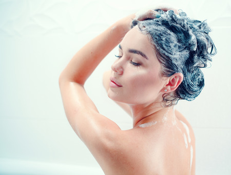 Beauty sexy model girl taking shower and washing her long black hair with a shampoo Stock Photo