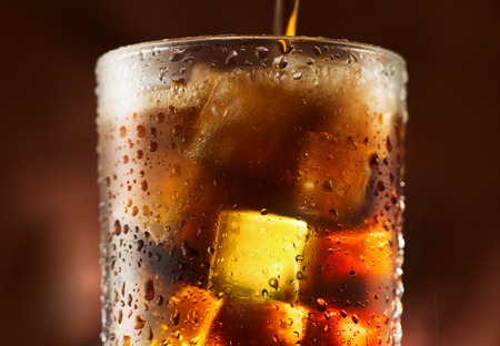 Cola pouring in glass with ice cubes over dark background Banco de Imagens - 83661549