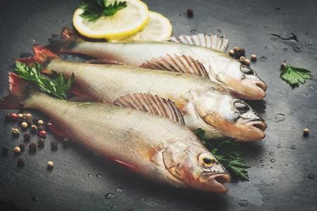 Verse vis met aromatische kruiden, kruiden, zout. Ruwe takken op donkere leisteenbak