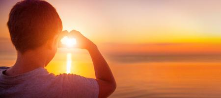 幸せな小さな少年の子供彼の手と心をかけて夕日海の背景。休暇の概念。夏の休日