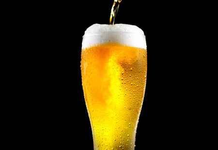 Beer. Cold craft light beer pouring in a glass with water drops