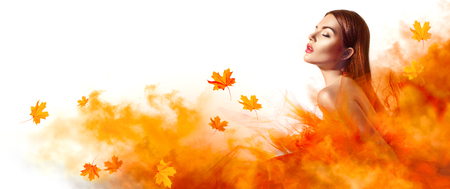 Beautiful fashion woman in autumn yellow dress with falling leaves posing in studio photo