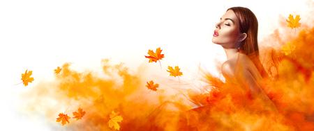 Beautiful fashion woman in autumn yellow dress with falling leaves posing in studio