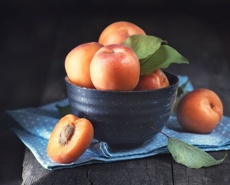 Apricots. Closeup of fresh organic apricot fruits in a bowl on dark rustic wooden table Stock Photo