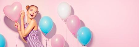Schoonheid blije tiener met kleurrijke luchtballonnen plezier over roze achtergrond Stockfoto