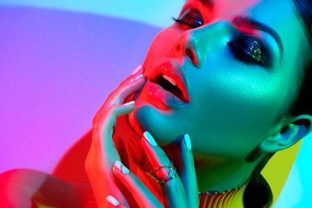 Fashion model vrouw in kleurrijke heldere lichten met trendy make-up en manicure poseren in de studio