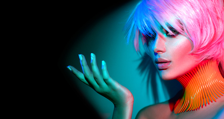 Mujer modelo de moda en coloridas luces brillantes, retrato de hermosa chica de fiesta con maquillaje de moda, manicura y corte de pelo Foto de archivo - 84326562