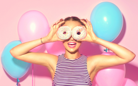 Joyful model beauty girl holding donuts and colorful air balloons over pink background