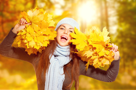 Beautiful model girl holding bunches of bright yellow autumn leaves