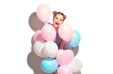 Beauty joyful teenage girl with colorful air balloons having fun isolated on white photo