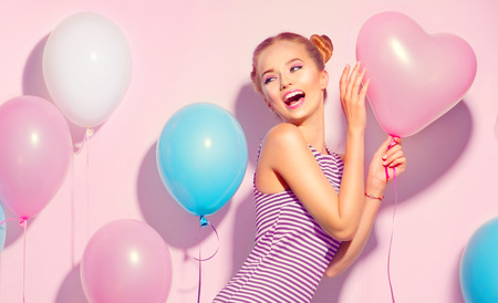 Beauty joyful teenage girl with colorful air balloons having fun over pink background Stock fotó