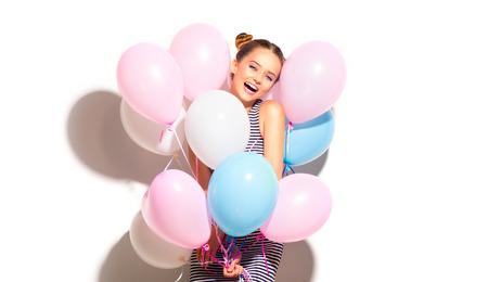 Beauty joyful teenage girl with colorful air balloons having fun isolated on white