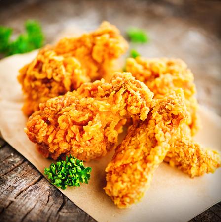 フライド チキンの翼および木製のテーブルの脚。おいしいフライド チキンのクローズ アップ