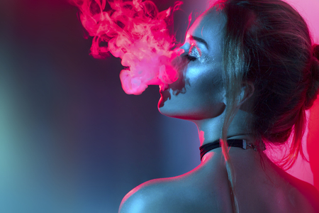 Fashion art portrait of beauty model woman in bright lights with colorful smoke. Smoking girl 스톡 콘텐츠