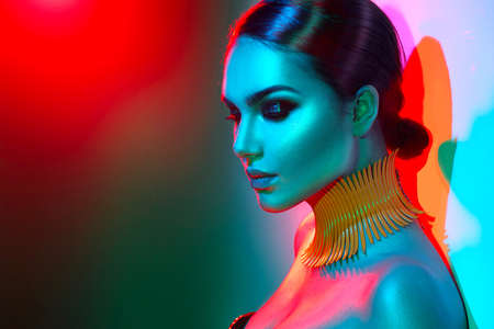 Fashion model woman in colorful bright lights posing. Portrait of beautiful girl with trendy makeup
