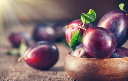 Plum. Juicy ripe organic plums closeup, over wooden background Standard-Bild