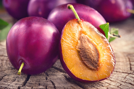 Plum. Juicy ripe organic plums closeup, over wooden background Banque d'images