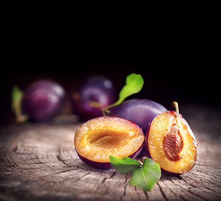 Plum. Juicy ripe organic plums closeup, over wooden background Stok Fotoğraf