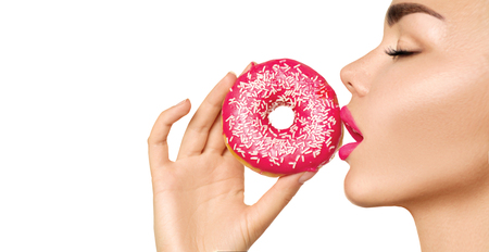 Beautiful woman eating pink donut. Beauty fashion model girl enjoying food over white