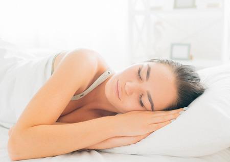 Beauty brunette girl sleeping in her comfortable bed Stock Photo